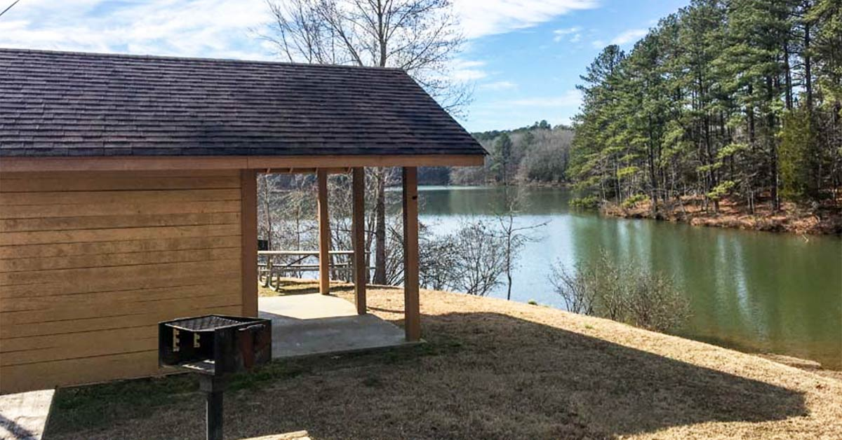 A small log cabin sits in front of Pin Oak Lake at Natchez Trace State Park