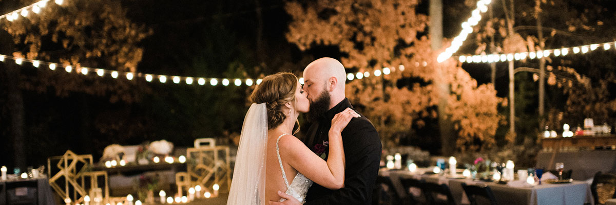 Couple kissing outdoors under string lights at Cedars of Lebanon